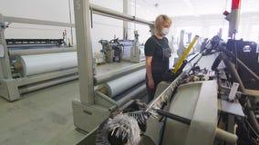 Η γυναίκα ελέγχει τη λειτουργία αργαλειών στο συνθετικό εργοστάσιο κατασκευής υφάσματος απόθεμα βίντεο