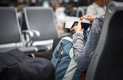 Η γυναίκα ελέγχει το εισιτήριό της διαβατηρίων και αεροπλάνων στο χέρι και την αναμονή του αεροπλάνου σε έναν διεθνή αερολιμένα,  στοκ εικόνες με δικαίωμα ελεύθερης χρήσης