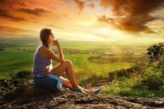 Η γυναίκα εξετάζει την άκρη του απότομου βράχου στην ηλιόλουστη κοιλάδα στοκ φωτογραφία