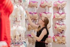 Η γυναίκα εξετάζει την τιμή στο στηθόδεσμο Διαφημίστε, πώληση, έννοια μόδας Γυναίκα που στέκεται στην υπεραγορά, που κοιτάζει μέσ στοκ φωτογραφία με δικαίωμα ελεύθερης χρήσης