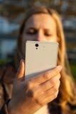 Η γυναίκα εξετάζει το άσπρο smartphone Στοκ Εικόνα