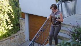 Η γυναίκα εξετάζει το τηλέφωνο σε ένα ραβδί selfie που έρχεται κάτω από τα σκαλοπάτια απόθεμα βίντεο