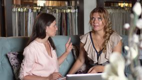 Η γυναίκα εξηγεί όλες τις επιχειρησιακές στιγμές στον πελάτη Δύο γυναίκες μιλούν μεταξύ τους σε έναν καναπέ στην υφασματεμπορία απόθεμα βίντεο