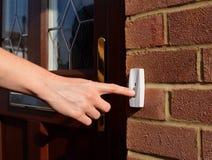 Η γυναίκα επεκτείνει το χέρι της στο δαχτυλίδι doorbell στοκ φωτογραφία