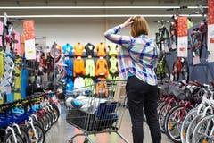 Η γυναίκα επιλέγει τα αγαθά στο αθλητικό κατάστημα Στοκ εικόνα με δικαίωμα ελεύθερης χρήσης