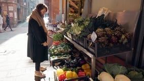 Η γυναίκα επιλέγει τα λαχανικά στην αγορά απόθεμα βίντεο