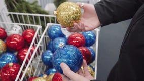 Η γυναίκα επιλέγει τα παιχνίδια Χριστουγέννων, κρατά στα χέρια της τις μπλε και χρυσές σφαίρες απόθεμα βίντεο