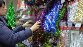 Η γυναίκα επιλέγει τις διακοσμήσεις διακοπών Χριστουγέννων στη λεωφόρο απόθεμα βίντεο