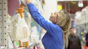 Η γυναίκα επιλέγει τις πάνες μωρών στην υπεραγορά Αγορές στο κατάστημα απόθεμα βίντεο