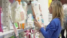 Η γυναίκα επιλέγει τις πάνες μωρών στην υπεραγορά Αγορές στο κατάστημα φιλμ μικρού μήκους