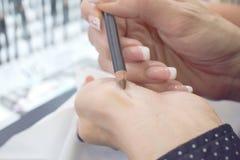 Η γυναίκα επιλέγει το μολύβι φρυδιών στο κατάστημα ομορφιάς στοκ φωτογραφίες