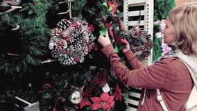 Η γυναίκα επιλέγει το στεφάνι Χριστουγέννων απόθεμα βίντεο
