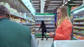 Η γυναίκα επιλέγει το τυρί στη γαλακτοκομική υπεραγορά τμημάτων απόθεμα βίντεο
