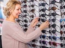 η γυναίκα επιλέγει τα γυαλιά ηλίου κοντά στην επίδειξη στοκ εικόνες με δικαίωμα ελεύθερης χρήσης