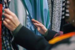 Η γυναίκα επιλέγει τα ενδύματα στο κατάστημα Στοκ Φωτογραφία