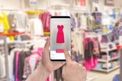 Η γυναίκα επιλέγει το φόρεμα, το μέγεθος και το χρώμα με το κινητό τηλέφωνο app Στοκ Εικόνες