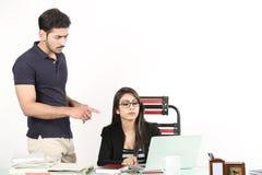 Η γυναίκα εργάζεται στο lap-top και ο άνδρας φαίνεται εργασία στο lap-top Στοκ Εικόνες