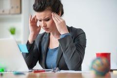 Η γυναίκα εργαζόμενος έχει τον πόνο στο κεφάλι της στοκ εικόνα