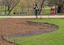 Η γυναίκα εργαζόμενος προετοιμάζει το χώμα στοκ εικόνες