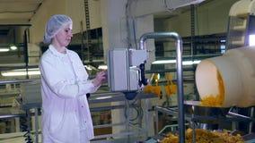 Η γυναίκα εργαζόμενος στέκεται σε μια δυνατότητα τροφίμων, που ελέγχει έναν μεταφορέα με τα πατατάκια απόθεμα βίντεο