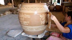 Η γυναίκα εργαζόμενος τυπώνει το σχέδιο δράκων με τον άσπρο άργιλο σε μεγάλο το βάζο φιλμ μικρού μήκους