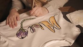 Η γυναίκα εφαρμόζει το σχέδιο σε μια άσπρη μπλούζα, κινηματογράφηση σε πρώτο πλάνο φιλμ μικρού μήκους