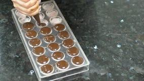 Η γυναίκα ζαχαροπλαστών βάζει τη σοκολάτα στη φόρμα στον πίνακα στην κουζίνα στο εσωτερικό απόθεμα βίντεο