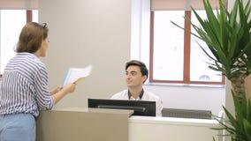 Η γυναίκα ζητά από τον άνδρα στην υποδοχή για να στείλει τα σημαντικά έγγραφα για τη διαχείριση απόθεμα βίντεο