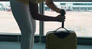 Η γυναίκα ζυγίζει τις αποσκευές της από συμπαγής weigher στον αερολιμένα απόθεμα βίντεο