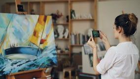 Η γυναίκα ζωγράφος παίρνει τη φωτογραφία της όμορφης εικόνας της χρησιμοποιώντας τη σύγχρονη κάμερα smartphone σχετικά με την οθό φιλμ μικρού μήκους