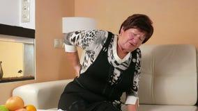 Η γυναίκα ηλικίας δεν μπορεί να κατεβεί επάνω τον καναπέ λόγω του πόνου στην πλάτη Τρίβει χαμηλότερο τον πίσω και πάσχει αυτήν τη φιλμ μικρού μήκους
