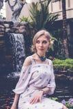 Η γυναίκα θέτει σε έναν τροπικό κήπο του νησιού του Μπαλί, Ινδονησία Καταρράκτης κήπων σε ένα υπόβαθρο Προκλητική νέα γυναίκα Στοκ εικόνα με δικαίωμα ελεύθερης χρήσης