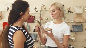 Η γυναίκα θαυμάζει τα μπεζ παπούτσια με το φίλο απόθεμα βίντεο