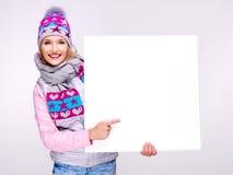 Η γυναίκα θερμό outerwear κρατά το έμβλημα και δείχνει σε το Στοκ Εικόνα