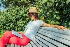 Η γυναίκα διαβάζει το βιβλίο στον πάγκο Στοκ φωτογραφία με δικαίωμα ελεύθερης χρήσης