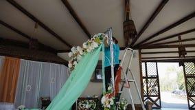 Η γυναίκα διακοσμεί τη γαμήλια αψίδα με το πράσινο ύφασμα απόθεμα βίντεο