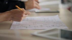 Η γυναίκα διενεργεί προσεκτικά τις προσαρμογές στο έγγραφο που βρίσκονται στον πίνακα φιλμ μικρού μήκους