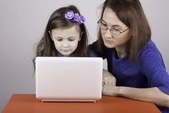 Η γυναίκα διδάσκει μια εργασία παιδιών για τον υπολογιστή Στοκ Εικόνες