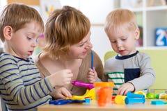 Η γυναίκα διδάσκει τα παιδιά handcraft στον παιδικό σταθμό ή το playschool Στοκ Φωτογραφία