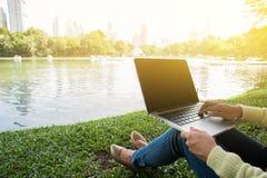 Η γυναίκα κάθεται για να χρησιμοποιήσει το lap-top στο πάρκο με το χρυσό φως Στοκ φωτογραφίες με δικαίωμα ελεύθερης χρήσης