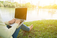 Η γυναίκα κάθεται για να χρησιμοποιήσει το lap-top στο πάρκο με το χρυσό φως Στοκ εικόνες με δικαίωμα ελεύθερης χρήσης