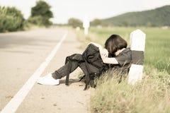 Η γυναίκα κάθεται με το σακίδιο πλάτης κάνοντας ωτοστόπ κατά μήκος ενός δρόμου Στοκ φωτογραφία με δικαίωμα ελεύθερης χρήσης
