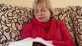 Η γυναίκα κάθεται σε έναν καναπέ και τα κτυπήματα μέσω των σελίδων του μεγάλου βιβλίου απόθεμα βίντεο