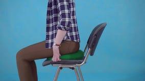 Η γυναίκα κάθεται σε ένα ορθοπεδικό μαξιλάρι σε μια καρέκλα σε ένα μπλε υπόβαθρο, η έννοια στενού επάνω hemorrhoids φιλμ μικρού μήκους