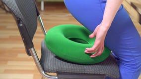 Η γυναίκα κάθεται σε ένα πράσινο ορθοπεδικό μαξιλάρι και παίρνει να εργαστεί κοντά επάνω, αργό MO φιλμ μικρού μήκους