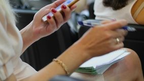 Η γυναίκα κάθεται σε μια καρέκλα και κρατά μια κινητή συσκευή με τη μάνδρα στο χέρι της στους ανθρώπους υποβάθρου απόθεμα βίντεο
