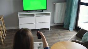 Η γυναίκα κάθεται σε μια καρέκλα, προσέχοντας τη TV με μια πράσινη οθόνη, που αλλάζει τα κανάλια με έναν τηλεχειρισμό Κλειδί χρώμ απόθεμα βίντεο