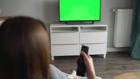 Η γυναίκα κάθεται σε μια καρέκλα, προσέχοντας τη TV με μια πράσινη οθόνη, που αλλάζει τα κανάλια με έναν τηλεχειρισμό Κλειδί χρώμ φιλμ μικρού μήκους