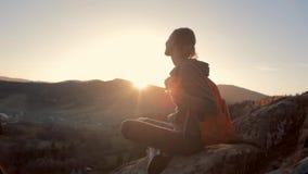 Η γυναίκα κάθεται στην άκρη του απότομου βράχου στο κλίμα της ανατολής απόθεμα βίντεο