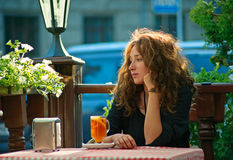 Η γυναίκα κάθεται στον καφέ στοκ εικόνα με δικαίωμα ελεύθερης χρήσης